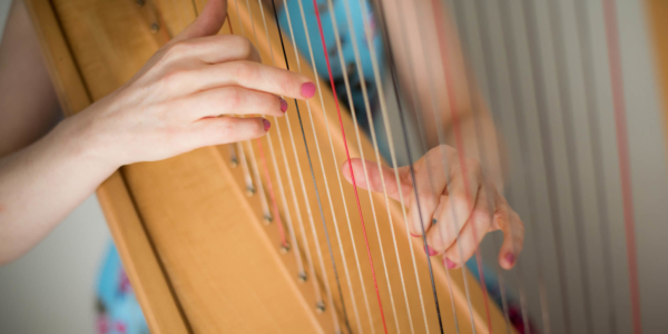 Bethan Nia playing her harp strings