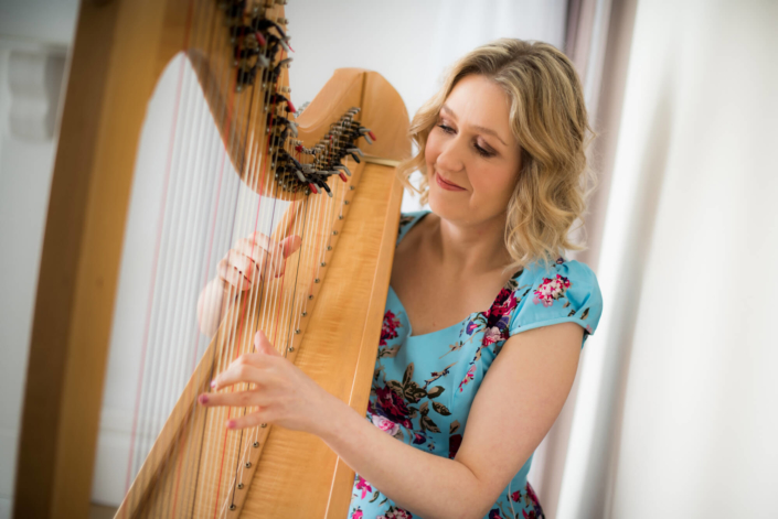 Bethan Nia posing and playing her harp