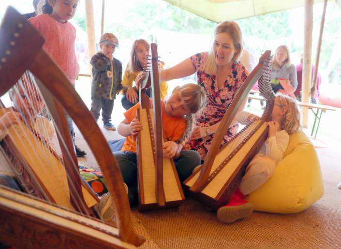 Bethan Nia teaching young kids to play the harp